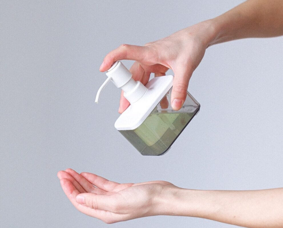 person squirting hand sanitizer into hand