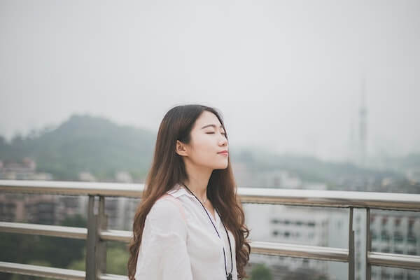 Woman taking a deep breath with eyes closed, relaxing