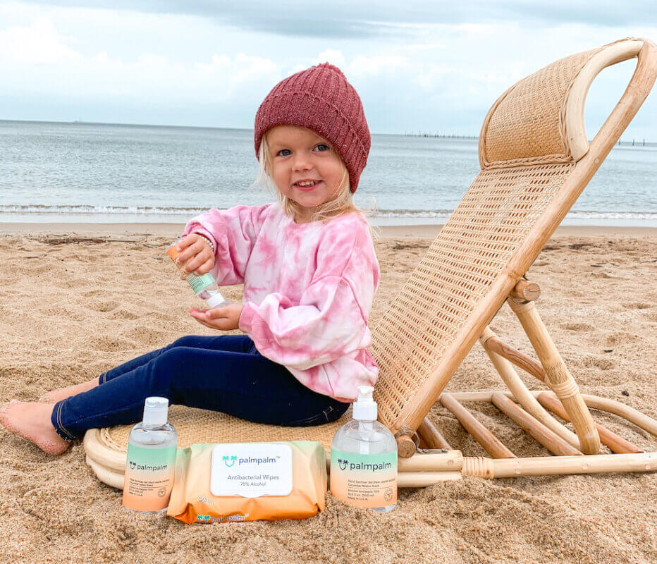 Child smiling and holding palmpalm hand sanitizer on the beach, surrounded by palmpalm hand sanitizer gel and wipes