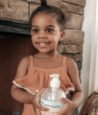 Child smiling and holding palmpalm hand sanitizer