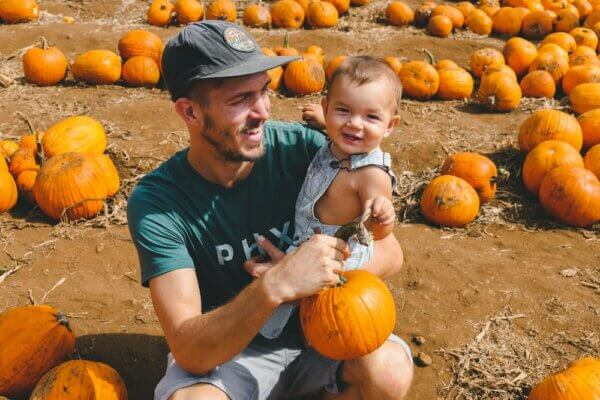 A father and child in a pumpkin patch