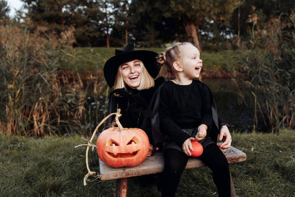 Young mother and child dressed up as witches for Halloween