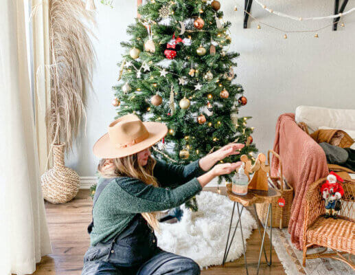 Woman sitting in front of Christmas tree putting on palmpalm hand sanitizer