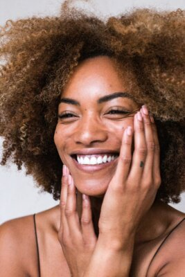Women holding her face and smiling, to show her skin